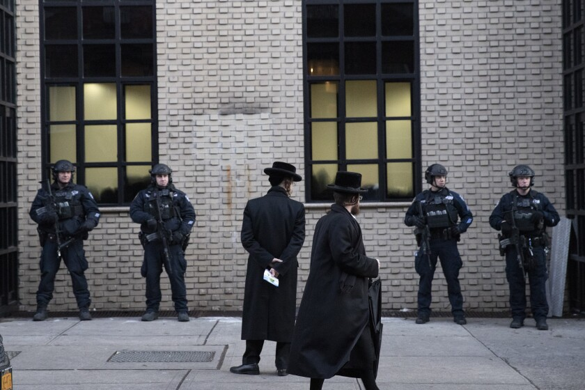 Orthodox Jewish men pass New York  police guarding a Brooklyn synagogue on Dec. 11.