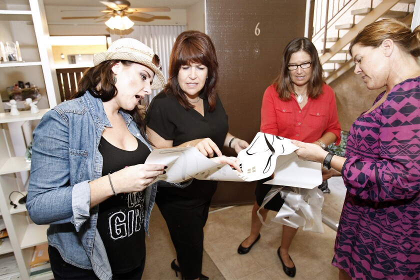 Jackie Schug, case manager for the two female tenants, interior designers Kathleen Garito and Leslie Deladurantey, and Tracy Rolfe, program manager at Aspiranet, from left, help decorate a home on Friday in Westminster. Newport Beach-based Interior Designers Institute is giving home makeovers and raising donations for former foster youth in Westminster.