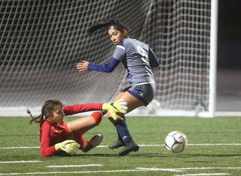 Los Alamitos goalie Reezyn Turk fights off a shot by Newport Harbor's Skyline Rodriquez during girls