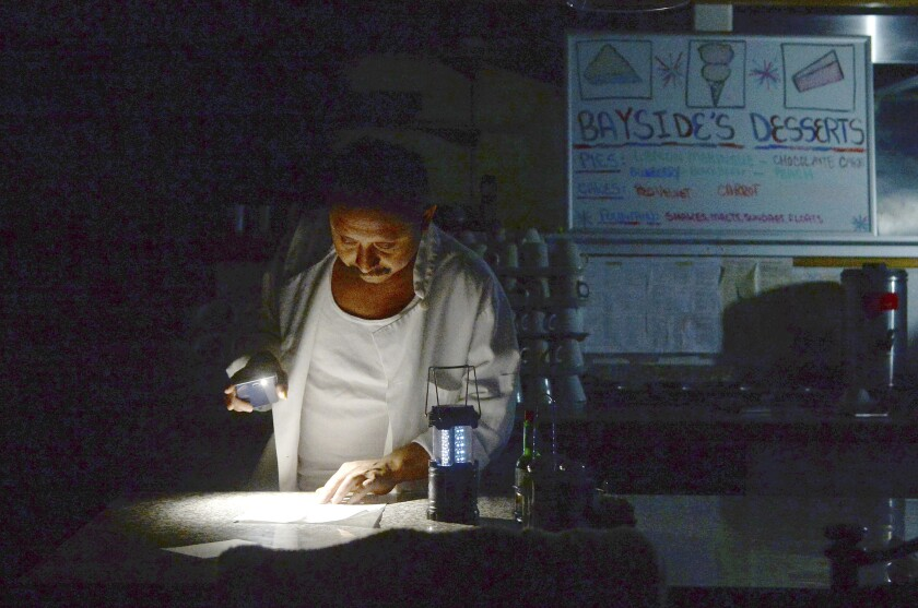 Carlos Lama of Bayside Cafe uses an LED lamp and light from his phone during a power outage