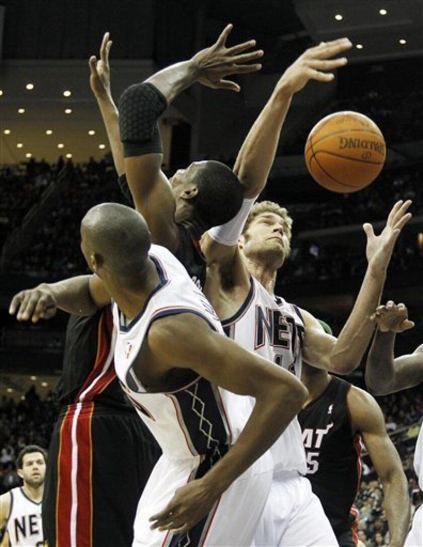 New Jersey Nets' Brook Lopez, right, and teammate Travis Outlaw, left, battle for the ball against Miami Heat's Chris Bosh during the second quarter of an NBA basketball game on Sunday, April 3, 2011, in Newark, N.J. (AP Photo/Julio Cortez)