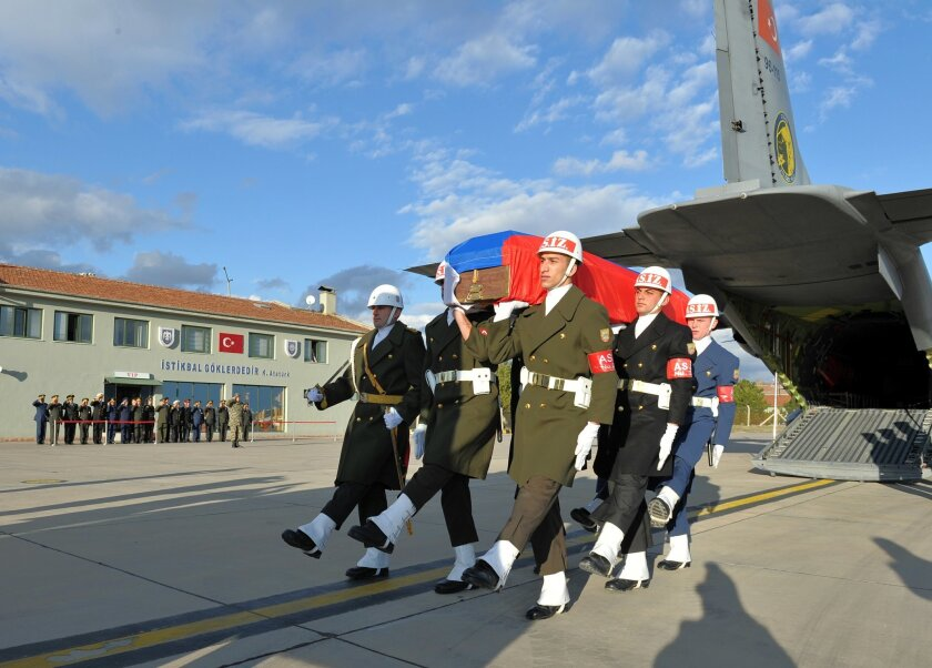 Turkish and Russian military officers, rear, salute as a Turkish honour guard carry the coffin of Russian pilot Lt. Col. Oleg Peshkov into a Russian Air Force transport plane at Esenboga Airport in Ankara, Turkey, Monday, Nov. 30, 2015. Early Saturday, Turkey had taken delivery of the body of Lt. Col Peshkov who was killed after Turkish F-16s shot down a Russian warplane near the Syrian-Turkish border last Tuesday. (Turkish Military, via AP)