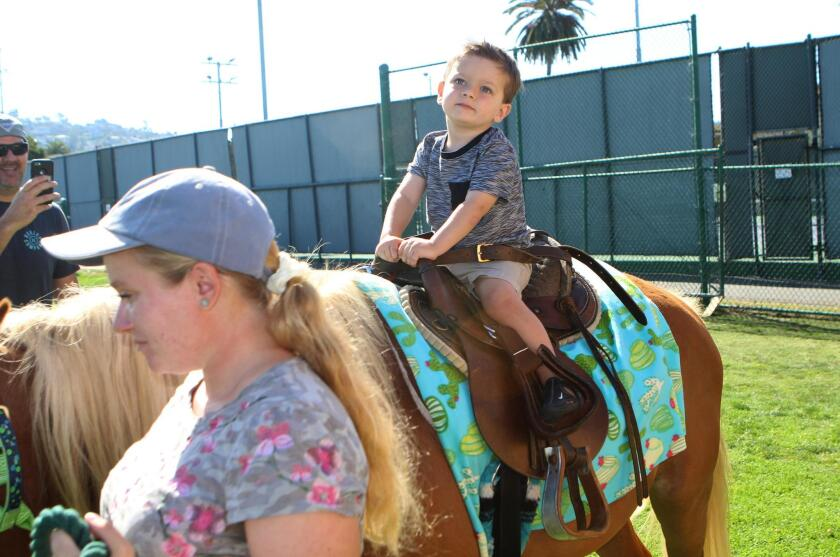 Clairemont resident Aidan Heyer, 2, gets a horsey ride on Sundance.