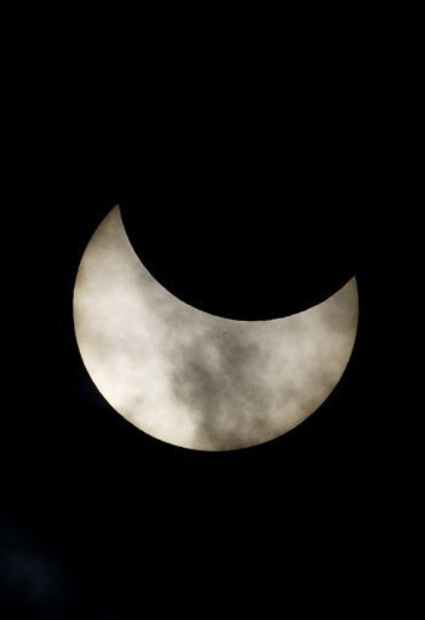 A view of a partial solar eclipse as seen from the town of Givatayim near Tel Aviv, Israel, Tuesday, Jan. 4, 2011. A partial solar eclipse began Tuesday in the skies over the Mideast and will extend across much of Europe. (AP Photo/Ariel Schalit)
