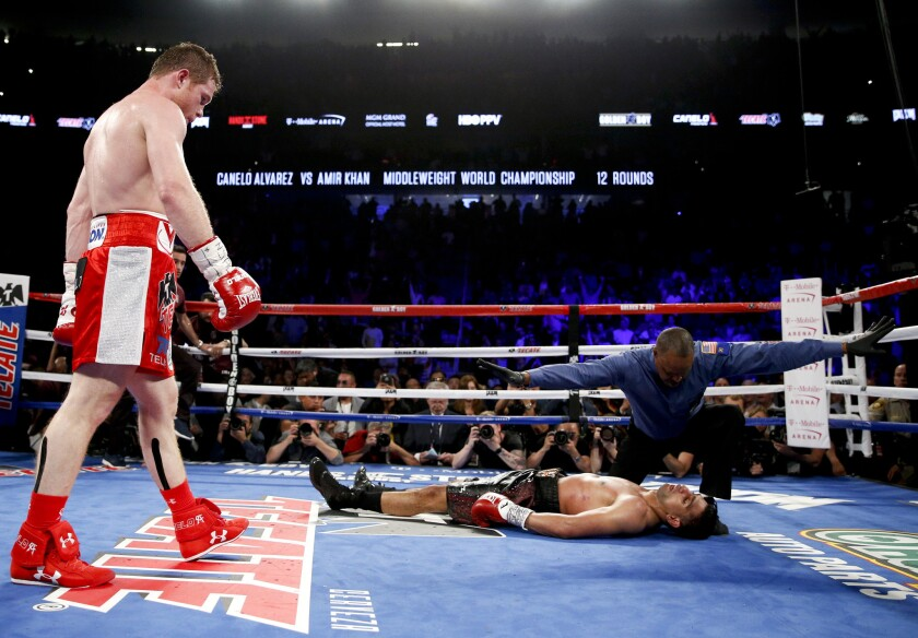 Amir Khan is counted out by the referee after getting knocked out by Canelo Alvarez in the sixth round of their WBC middleweight title fight Saturday at T-Mobile Arena in Las Vegas.