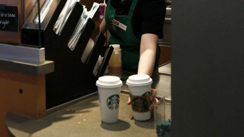 A Starbucks barista moves drinks.