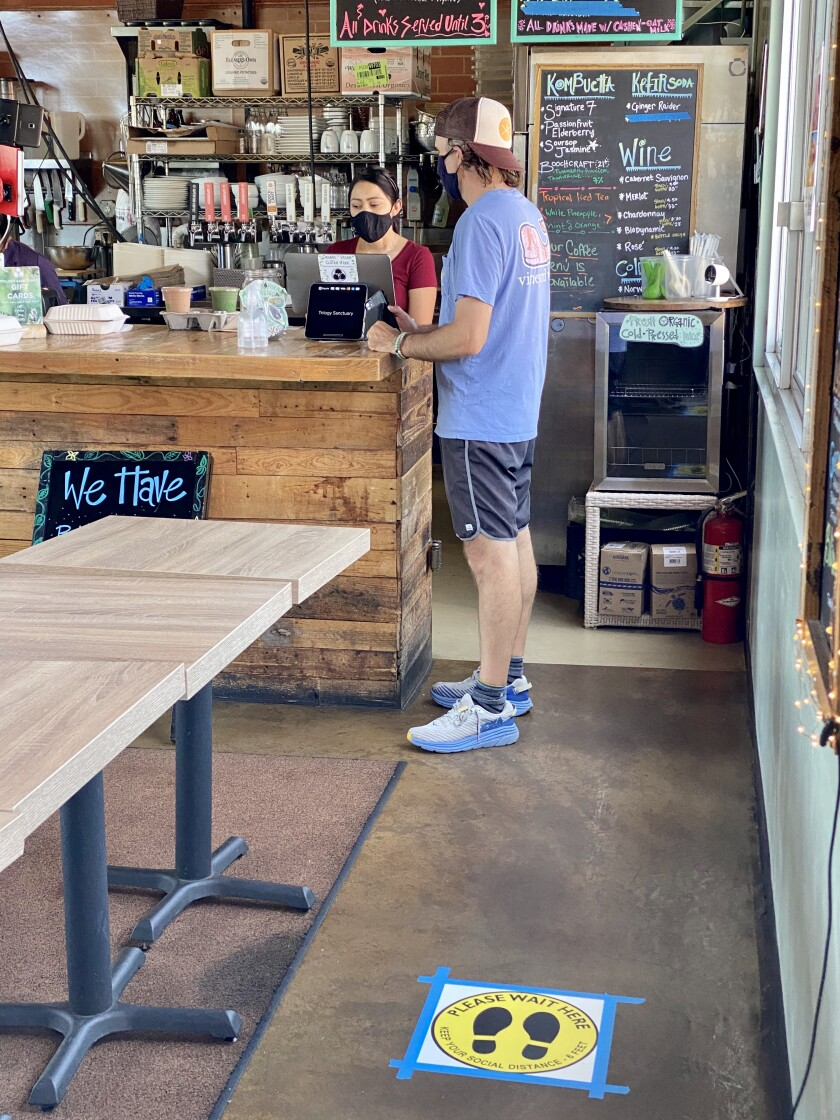 A masked employee serves a customer at La Jolla's Trilogy Sanctuary vegan cafe in May 2020.
