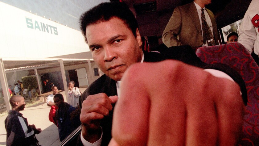 Former heavyweight champion Muhammad Ali throws playful punch toward a photographer while sitting on a bus in front of Locke High School in December 1996.