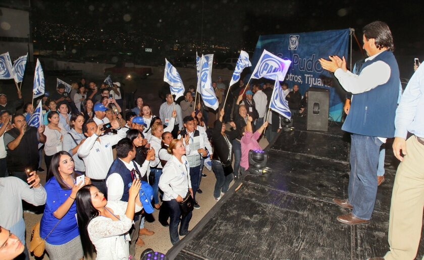 Juan Manuel Gastelum, at right, the PAN Party candidate for Tijuana Mayor, applauds his supporters from a stage at the party's Tijuana headquarters on election night. On Saturday, he was formally declared mayor-elect.
