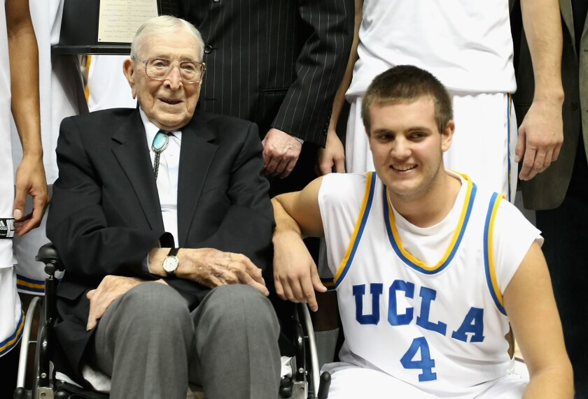 Legendary UCLA coach John Wooden poses with great-grandson Tyler Trapani following a game in 2008.