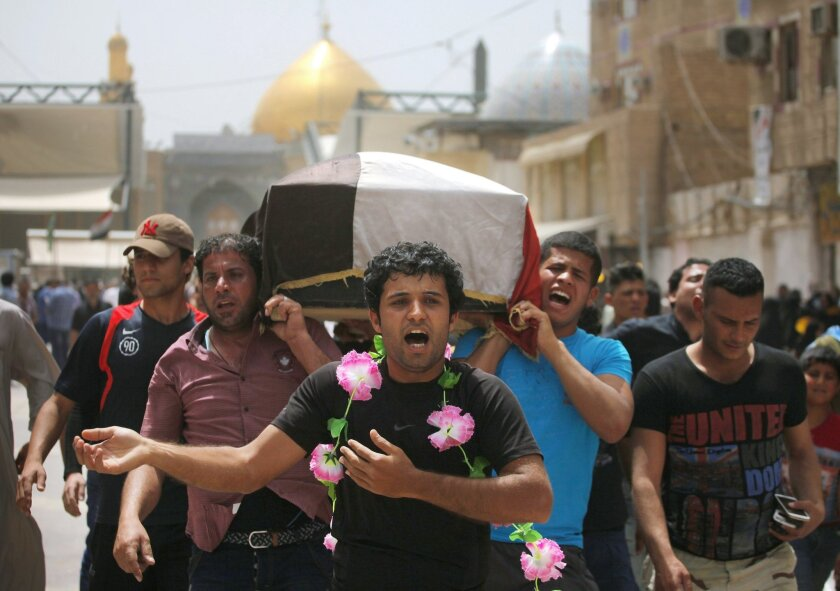 Friends of Mustafa Mounir, 19, chant slogans against the al-Qaida breakaway group Islamic State of Iraq and the Levant (ISIL), while carrying his flag-draped coffin during his funeral procession in Najaf, 100 miles (160 kilometers) south of Baghdad, Iraq, Friday, April 18, 2014. Mustafa Mounir was killed in a car bomb attack in Baghdad on Thursday, his family said. (AP Photo/Jaber al-Helo)