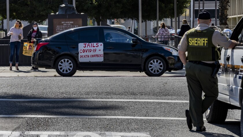 A Riverside County sheriff's deputy keeps watch during a car rally to protest conditions in Riverside County jails, where there has been a coronavirus outbreak.