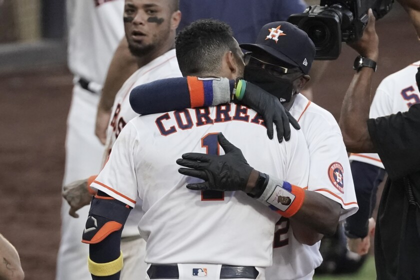 Houston Astros Carlos Correa is hugged by Houston Astros manager Dusty Baker Jr. after his walk off home run during the ninth inning in Game 5 of a baseball American League Championship Series, Tuesday, Dec. 15, 2020, in San Diego. The Astros defeated the Rays 4-3 and the Rays lead the series 3-2 games. (AP Photo/Ashley Landis)