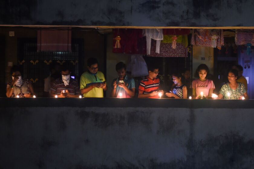 Residents of Mumbai light candles and turn on their mobile phone lights to observe a vigil called by Indian Prime Minister Narendra Modi to show unity against the coronavirus pandemic on Sunday.