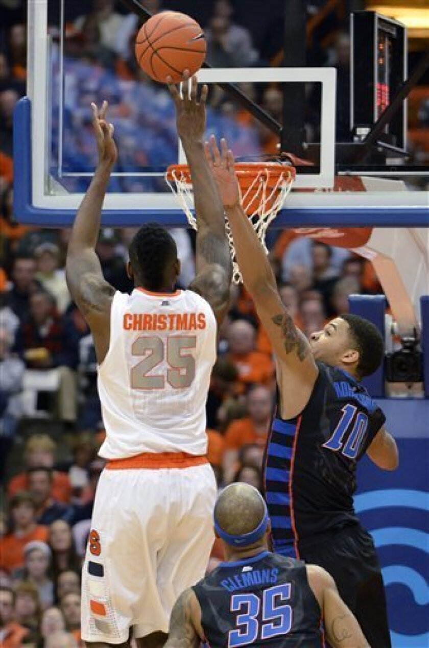 Syracuse's Rakeem Christmas scores against DePaul's Derrell Robertson during the first half of an NCAA college basketball game in Syracuse, N.Y., Wednesday, March 6, 2013. (AP Photo/Kevin Rivoli)