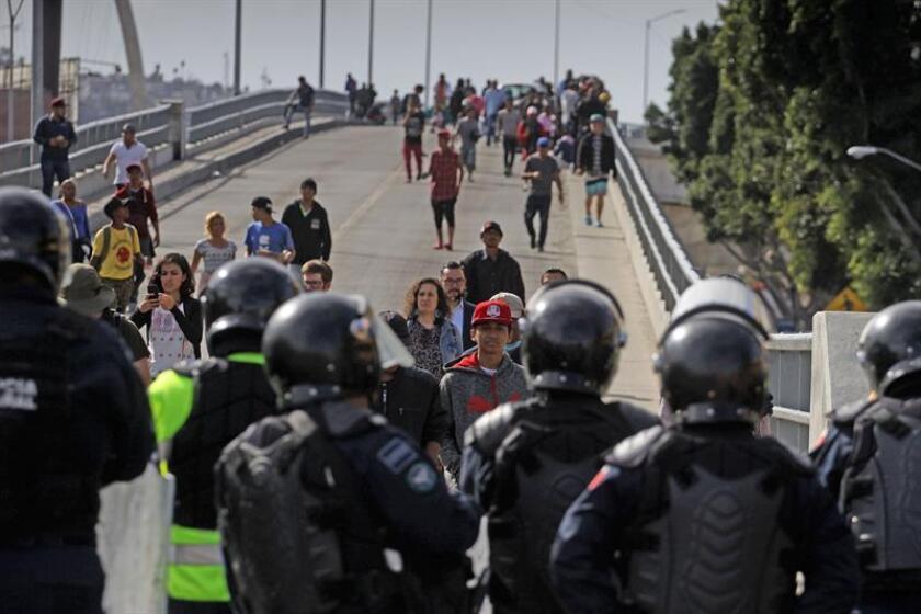 Agentes federales y municipales mexicanos bloquean a unos 200 migrantes centroamericanos que marchan hoy del albergue que ocupan en la zona norte de Tijuana (México) a la garita peatonal de El Chaparral con el objetivo de solicitar asilo ante autoridades estadounidenses. EFE