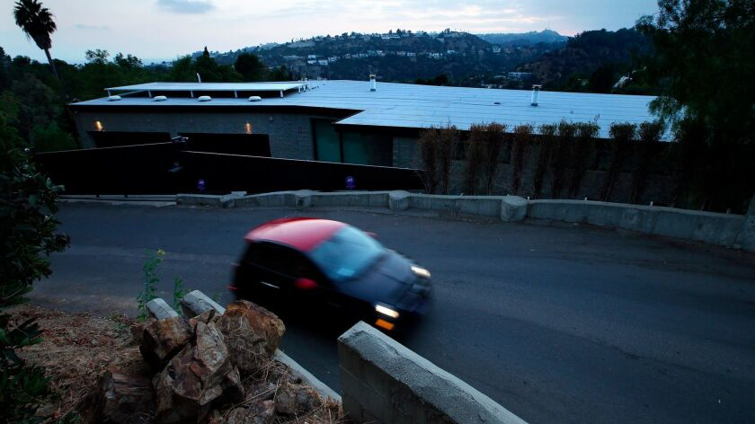 A motorist drives along La Cuesta Drive in the Hollywood Hills, past a home that was cited by the L.
