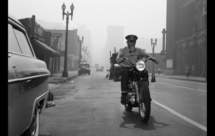 Motorcycle messenger Frank Stone uses a gas mask while making deliveries Sept. 14, 1955.