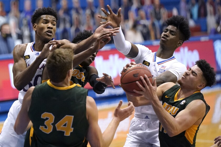 North Dakota State's Jarius Cook, lower right, beats Kansas' Ochai Agbaji, left, and Tyon Grant-Foster, upper right, to a rebound during the second half of an NCAA college basketball game Saturday, Dec. 5, 2020, in Lawrence, Kan. (AP Photo/Charlie Riedel)