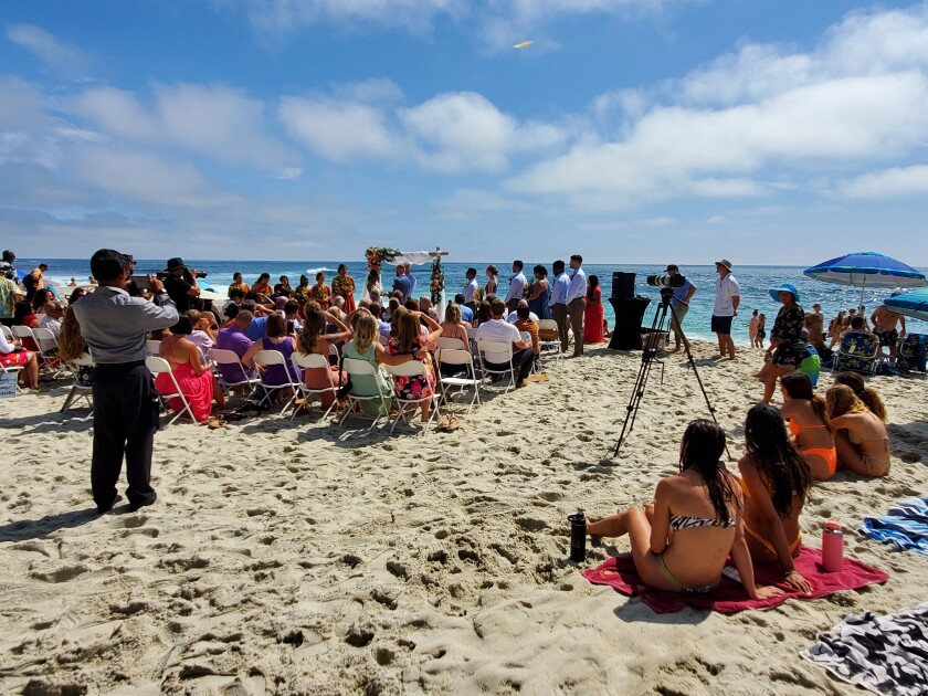 A wedding takes place at Windansea Beach on July 10, with several beach-goers nearby.