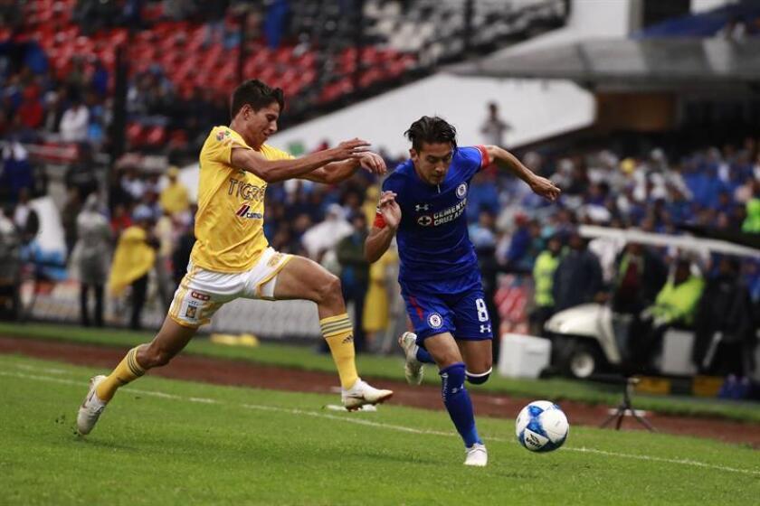 Javier Salas (d), del Cruz Azul, fue registrado este sábado al intentar superar la marca de Jürgen Damm (i), de Tigres de UANL, durante un partido correspondiente a la tercera jornada del Torneo Apertura del fútbol en México, en el estadio Azteca de la Ciudad de México (México). EFE