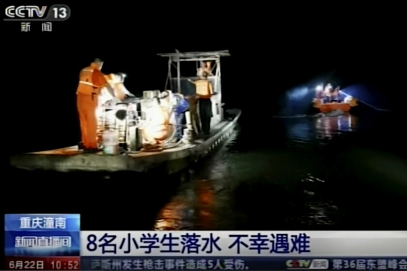 An image taken from China's CCTV video shows rescue workers searching along a river in China's Chongqing province.