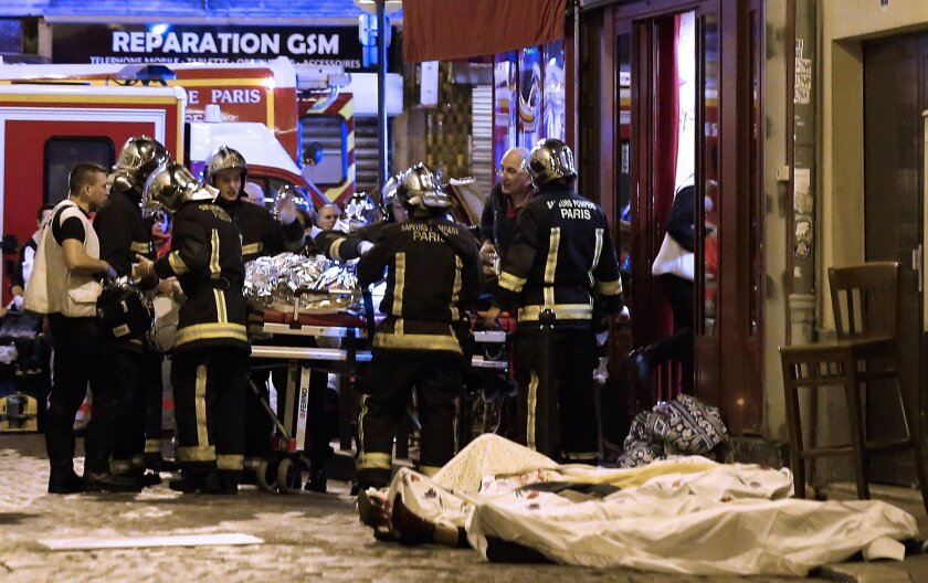 FILE - In this Friday, Nov. 13, 2015 file photo, rescue workers tend to victims in the 10th district of Paris. The jihadi network that recruited and groomed one of the suicide attackers in the Nov. 13 attacks in Paris is on trial, on the week starting Monday, May 30, 2016. Defendants include the br