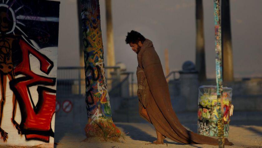 VENICE, CA DECEMBER 6, 2017: At dawn, a homeless man walks around Venice Beach wearing a blanket N