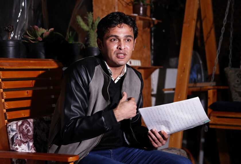 Rami Aman, a Palestinian Gazan peace activist, holds note's in which he recalled his ordeal, during an interview on the roof of his family house in Gaza City, Feb. 10, 2021. After months of torture and interrogations in a Hamas prison, Aman says he was offered an unconventional proposition: Divorce your wife and you are free to go. Aman had recently signed a marriage contract with the daughter of a Hamas official, and the ruling Islamic militant group apparently wanted to dispel any insinuation that it supported Aman's outreach to Israeli peace activists. (AP Photo/Adel Hana)