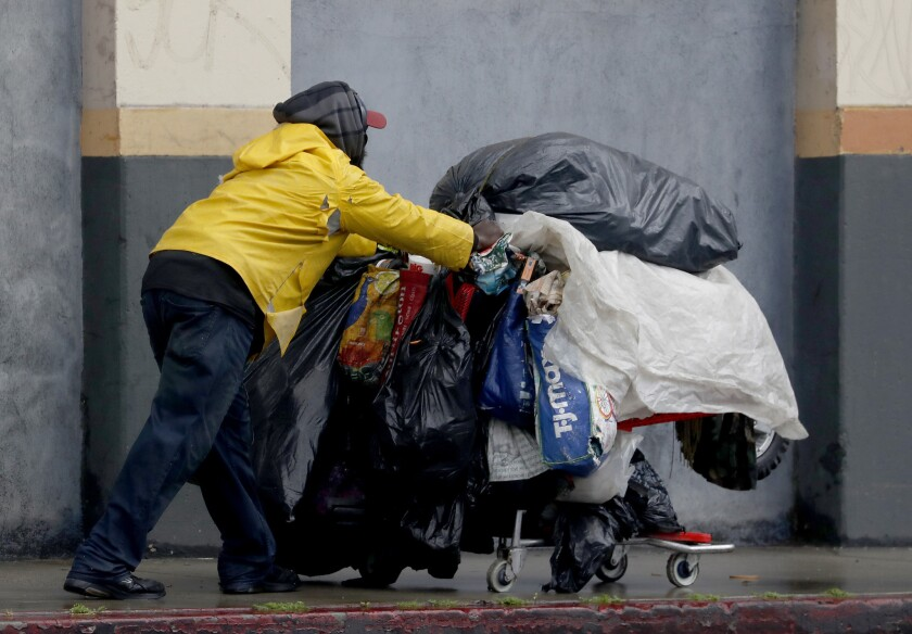 LOS ANMGELES, CALIF. - MAR. 6, 2019. A homeless pushes a shopping cart filled with his belongings do