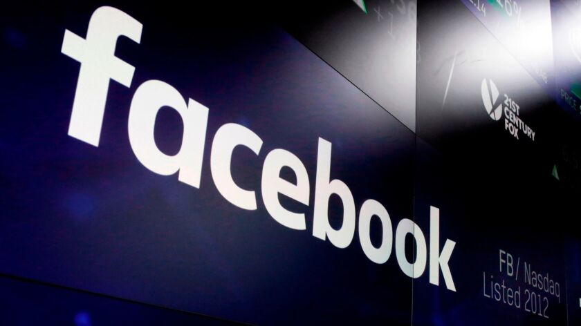 FILE - This March 29, 2018 file photo shows the Facebook logo on screens at the Nasdaq MarketSite in