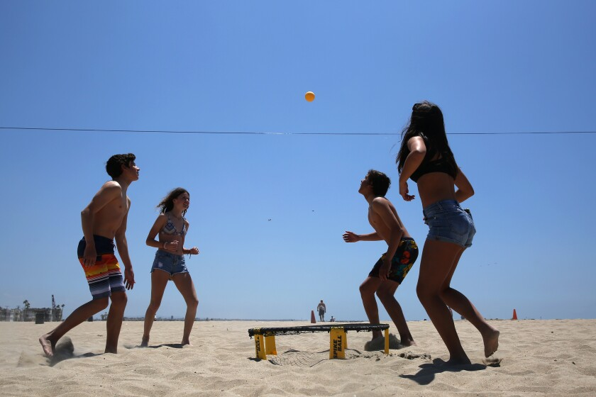 Shawn Jones, left, Yari Perkins, Kalani Delarole and Keira Toor play spike ball in Seal Beach on Monday.