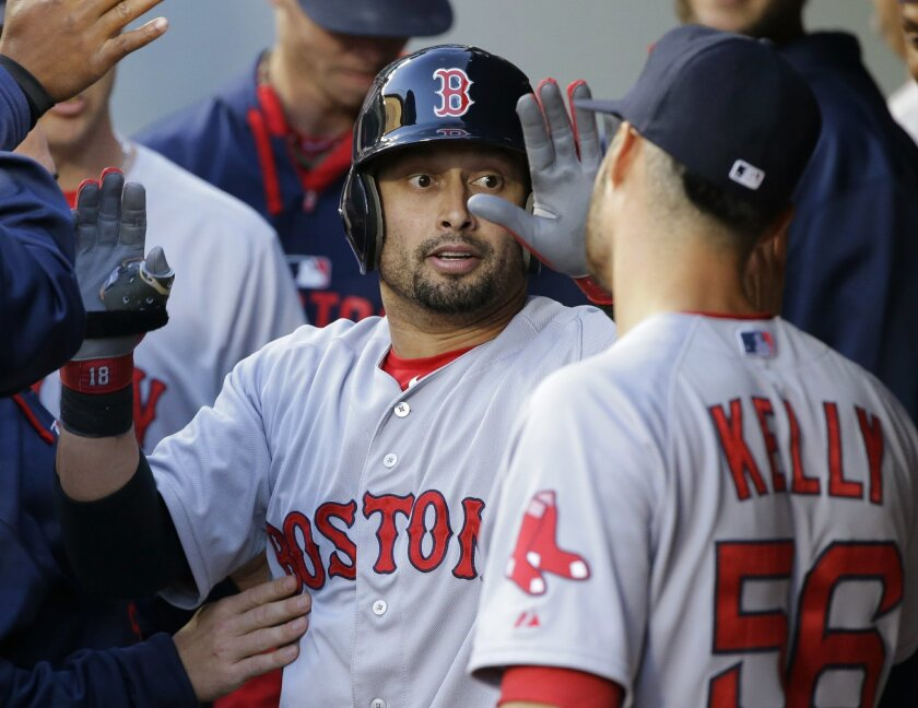Boston Red Sox's Shane Victorino is greeted in the dugout by starting pitcher Joe Kelly, right, after Victorino hit a solo home run in the fourth inning of a baseball game against the Seattle Mariners, Thursday, May 14, 2015, in Seattle. (AP Photo/Ted S. Warren)