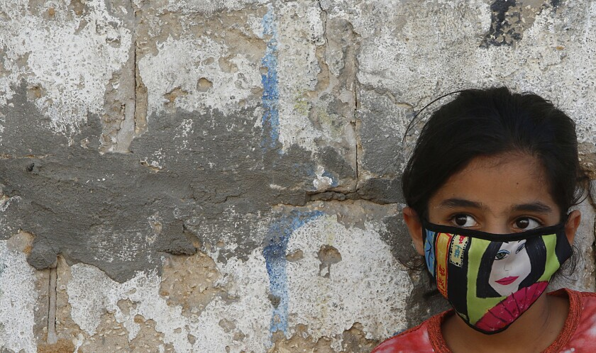 A Palestinian girl wears a face mask in the Gaza Strip