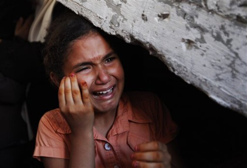 A girl cries as the bodies of Palestinian militants Ziyad Raadi and Mahmoud Mortada, who were cousins, are carried into the family house in Nusseirat refugee camp, central Gaza Strip, during their funeral procession,Tuesday June 8, 2010. The bodies of the two Palestinians killed by Israeli forces' fire in the waters off Gaza before dawn Monday, were washed ashore Tuesday, bringing to six the total number of militants from the Al-Aqsa Martyrs' Brigades _ the remnants of a violent offshoot of Palestinian President Mahmoud Abbas' Fatah faction _ killed by the Israeli navy in the raid. (AP Photo/Lefteris Pitarakis)