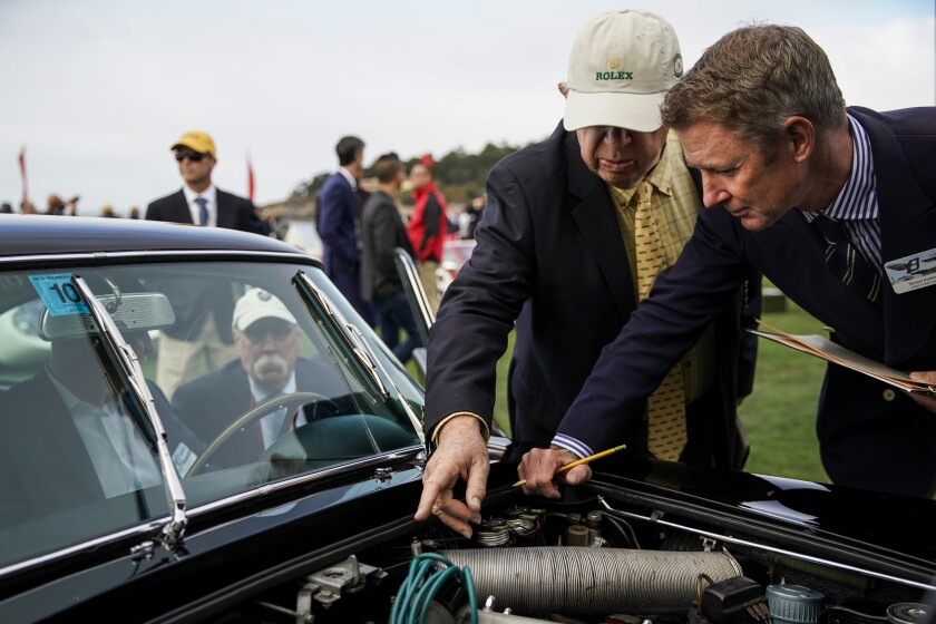 Judge Jerry F. Rosenstock, left, and Chief Class Judge Simon Kidston inspect a 1965 Aston Martin DB5 Vantage coupe at the Concours d'Elegance.
