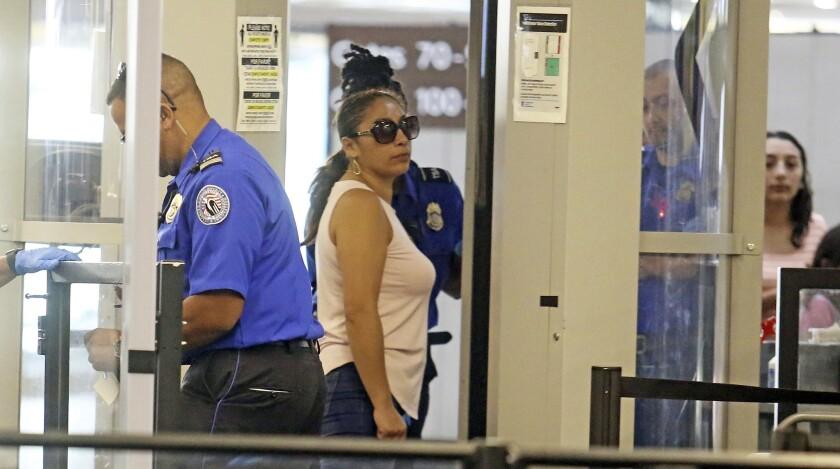 CORRECTS AGE TO 39-Alejandra Juarez,39, center, passes through TSA screening at the Orlando Internat