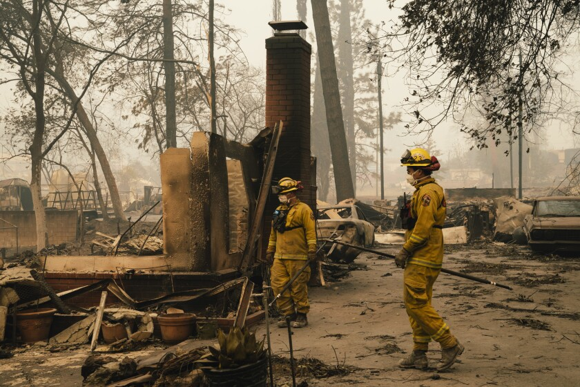 Firefighters stand in the remains of a house burned in the Camp Fire in Paradise, Calif., in 2018.