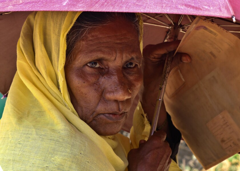 A Rohingya refugee woman waits to collect food aid at the Kutupalong refugee camp in Bangladesh.