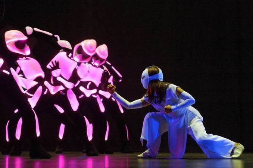 """LaMae Capares as Karate Girl with robots in La Jolla Playhouse's production of """"Yoshimi Battles the Pink Robots."""""""