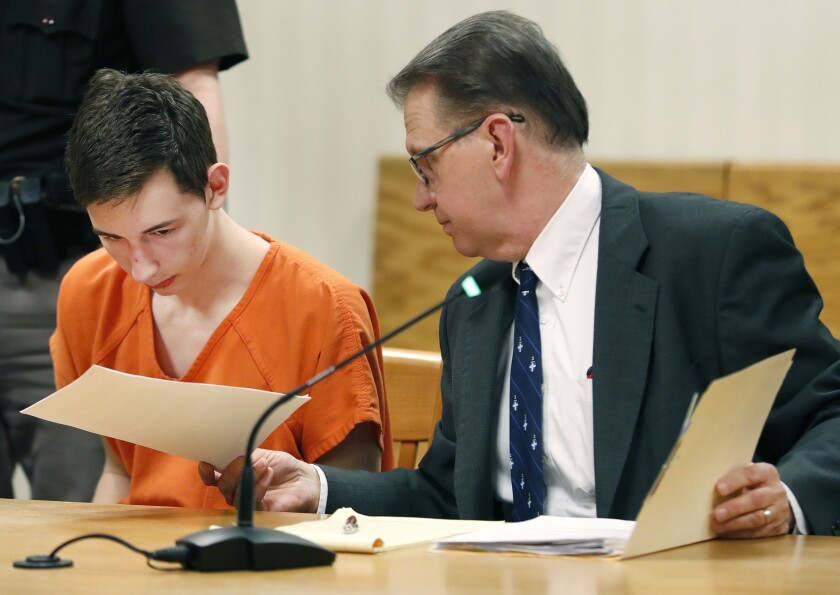 FILE - In this April 16, 2019 file photo, Alexander M. Kraus, is handed documents by his attorney Gregory Petit during his initial appearance in the Outagamie County Circuit Court in Appleton, Wis. A jury ruled Thursday, June 11, 2021, that Kraus, who pleaded guilty to fatally shooting his grandparents in 2019, is criminally responsible for the deaths. He now faces two life prison terms when he's sentenced Aug. 16. (Danny Damiani/The Post-Crescent via AP, File)