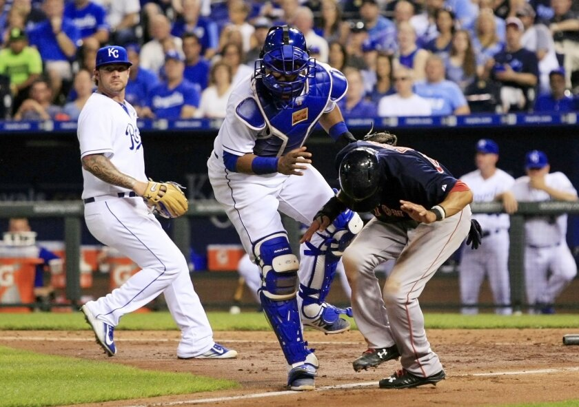 Boston Red Sox'  Mookie Betts, right, is tagged out by Kansas City Royals' catcher Salvador Perez, center, during a rundown as pitcher Brandon Fannegan provides backup in the seventh inning of a baseball game at Kauffman Stadium in Kansas City, Mo., Friday, June 19, 2015. Betts was caught attemptin