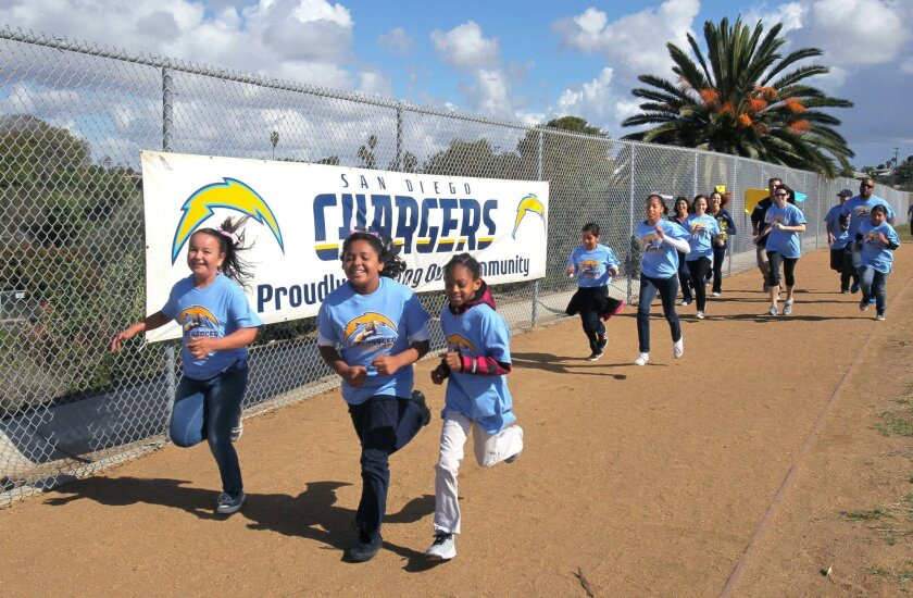 Laurel Elementary students Jessica Morales, (from left) Leslie Alaniz, and Samantha Benjamin run on their new track after its dedication Tuesday. The Chargers Champions Grant Program donated $30,000 for the track.