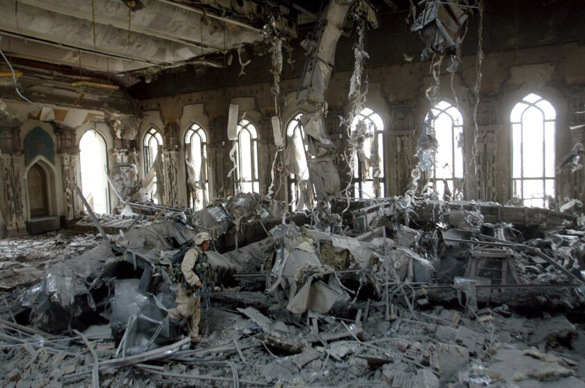 A soldier is seen amid masses of rubble inside a building with rows of ornate windows in the background.