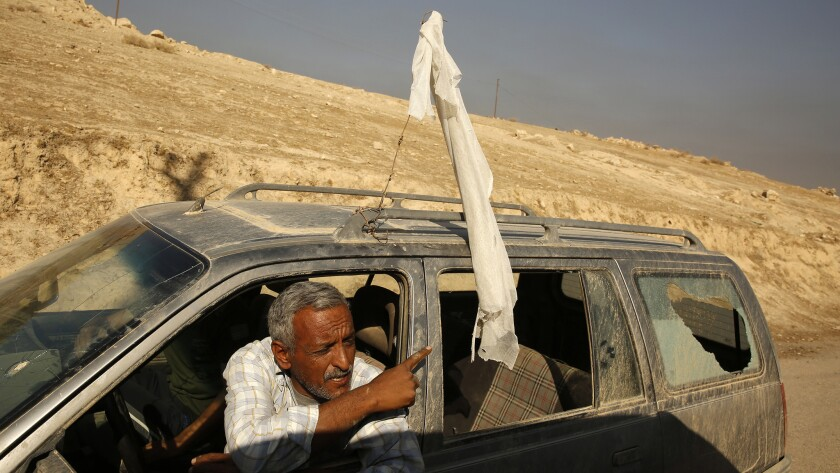 A man flying a white flag with his rear window shattered, is stopped on the road from Salhyia to Qayarrah on Thursday.