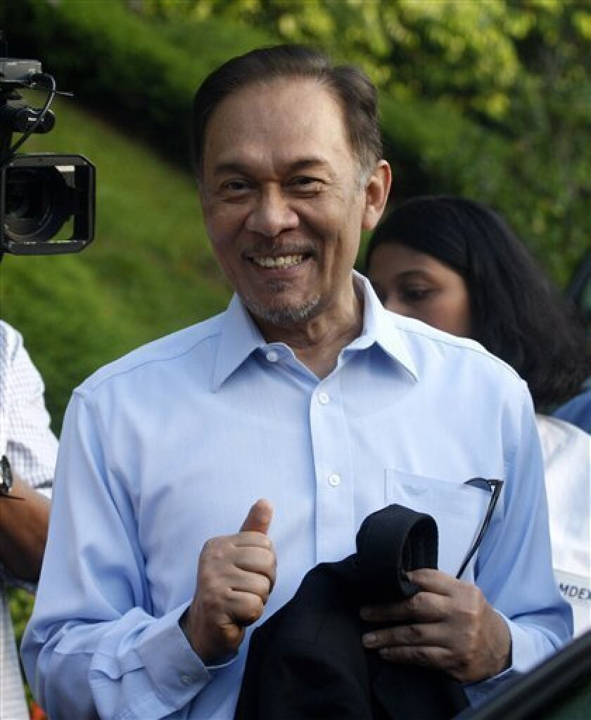 Malaysian opposition leader Anwar Ibrahim shows a thumbs-up as he prepares to leaves his residence to the High Court for his sodomy trial verdict in Kuala Lumpur, Malaysia, Monday, Jan. 9, 2012. (AP Photo/Lai Seng Sin)