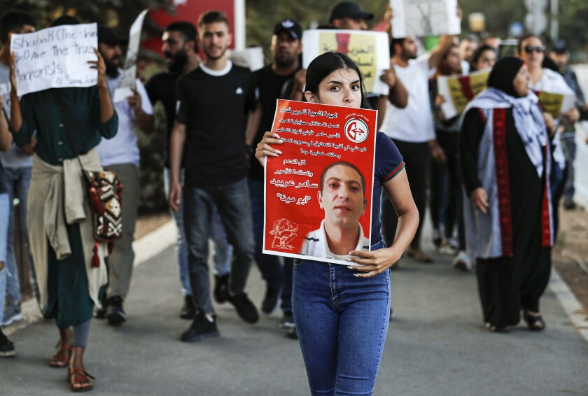 A woman holds a poster of Samer Arbeed, a Palestinian arrested by Israeli authorities