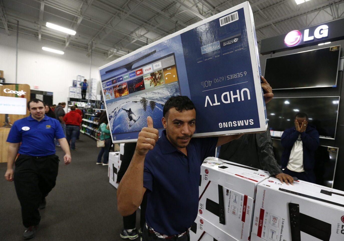 """Un hombre posa para el fotógrafo con una televisión en una tienda en Mesquite, Texas. Estados Unidos celebra la jornada de compras conocida como """"viernes negro"""" (""""Black Friday""""), que da inicio a las rebajas y a la mayor temporada de consumo del año, que se prolonga hasta las navidades."""