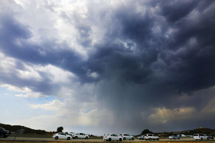 Cars move slowly along the northbound 14 freeway in the Santa Clarita area Wednesday as storm clouds and rain pass over the area.