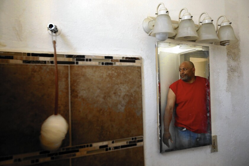 Bruce Smith, reflected in the mirror, looks over his bathroom that doesn't have a shower head or faucet. The Long Beach apartment, which he has been living in for two years with Larry Watson, has no running water.